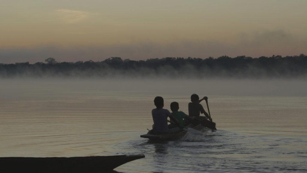 Imagem da silhueta de três meninos em uma canoa, remando em um rio, em direção à floresta. A foto parece ter sido tirado no anoitecer.