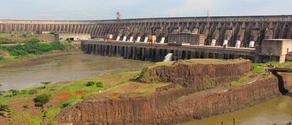 The frontal structure of a hydroelectric dam, in gray concrete, appears in the back of the photo. In front of it are streams of water being released into a gray river. Near the edges of the image, the sides of the structure rest upon a ground covered in thin, light green grass. Near the upper edge of the photo is a thin strip of light blue sky.