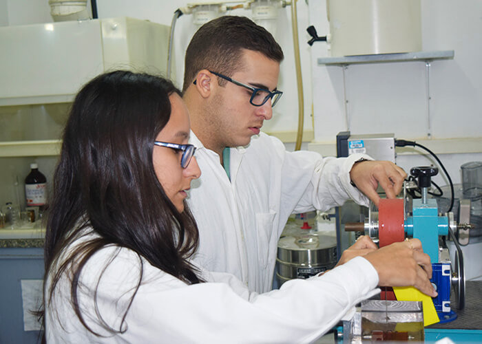 A young woman and a young man, side by side, are handling lab equipment. The man is further to the back in the photo, has white skin, short brown hair, and is wearing square glasses with green frames. The woman is towards the front, has white skin, long and straight dark brown hair, and is wearing square glasses with dark blue frames. Both are wearing long sleeved white lab coats, and are on the left side of the photo, facing the right side, where the equipment they are handling is. This equipment is made up of rectangular metallic recipients colored blue, red and yellow, and are connected to each other by cylindrical tubes. There is a black plastic handle on the top of it. In the background is a white wall with shelves and various pieces of equipment.