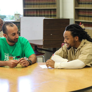 A young white man, bearded and slightly bald, wearing a green shirt, sits at a round wooden table, talking to another man, who is black, with goatee and dreadlocks, wearing a prisoner's uniform (pants and beige shirt). In the background, two large bookshelves and other round tables.