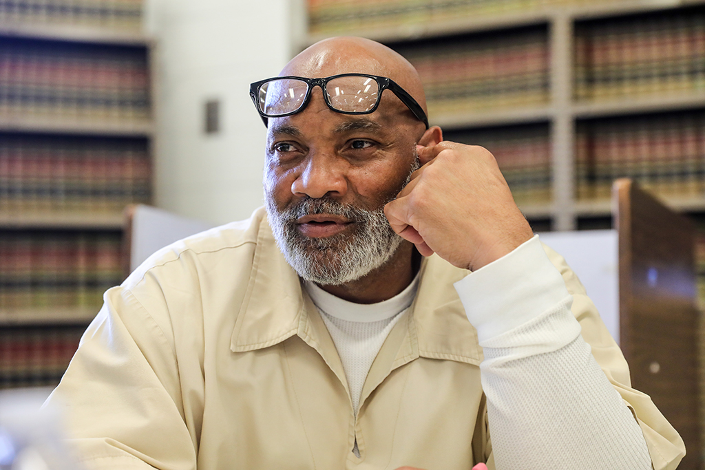 A bald, black man with a gray beard, and glasses resting on his forehead. He wears a long white shirt under a short-sleeved beige shirt. He is looking to his right and seems to be talking to someone.