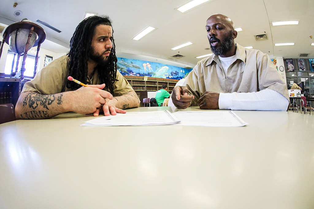 Two men, seated at a table, talking and holding pens in their hands. The man on the left looks about 25 years old. He is black, has dreadlocks and, on his arm, tattoos. The other man, on the right, is black, bald, with a beard, and appears to be around 40 years old.