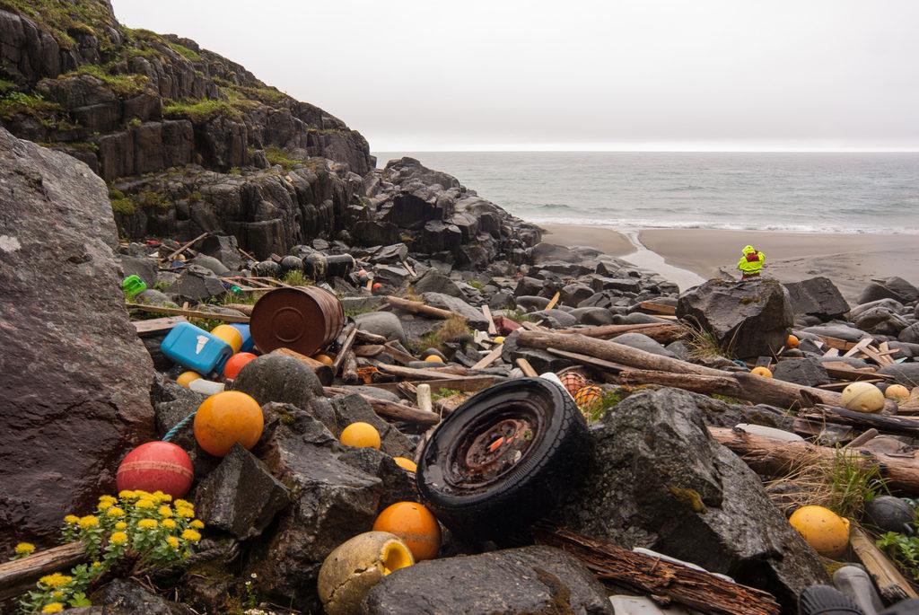Um rochedo está coberto por resíduos diversos, espalhados, dentre os quais há pneus, bolas de plástico coloridas, barris de metal e pedaços de madeira. Ao fundo, um trecho de areia escura, o mar, e o céu, acinzentado.