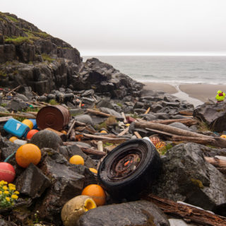 A rocky shore is littered with a variety of waste, among them tires, colored plastic balls, metal barrels and pieces of wood. In the back is a thin strip of dark sand, the sea, and a gray sky.