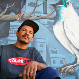 A black man with a beard and mustache is wearing a black cap and a black T-shirt. He is looking at the camera, with a serious expression. Behind him, on a wall, is a graffiti mural depicting a large bird on a tree branch, with apartment buildings in the background.