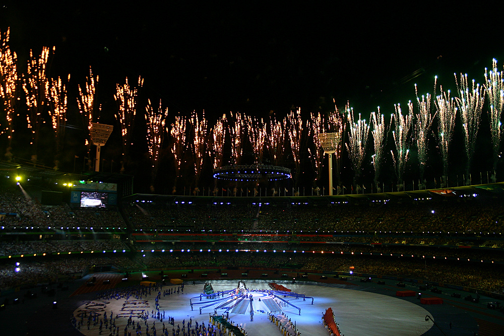 The photo shows a big stadium at night, with fireworks being launched around its circular roof. Inside the stands are filled with people. In the center, people can be seen lining up on the field in a ceremony. The field is white.