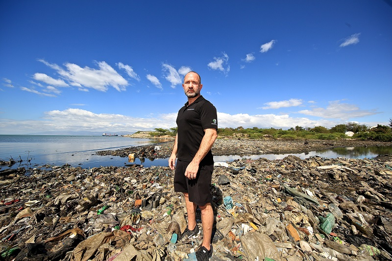 A thin man with white skin, short gay hair and beard, wearing all black (polo shirt, shorts and sneaker) is standing facing the left side of the photo and looking at the camera. The ground around him is covered in plastic waste, ending in the sea behind him. At the top of the picture, above the landscape, is a bright blue sky.