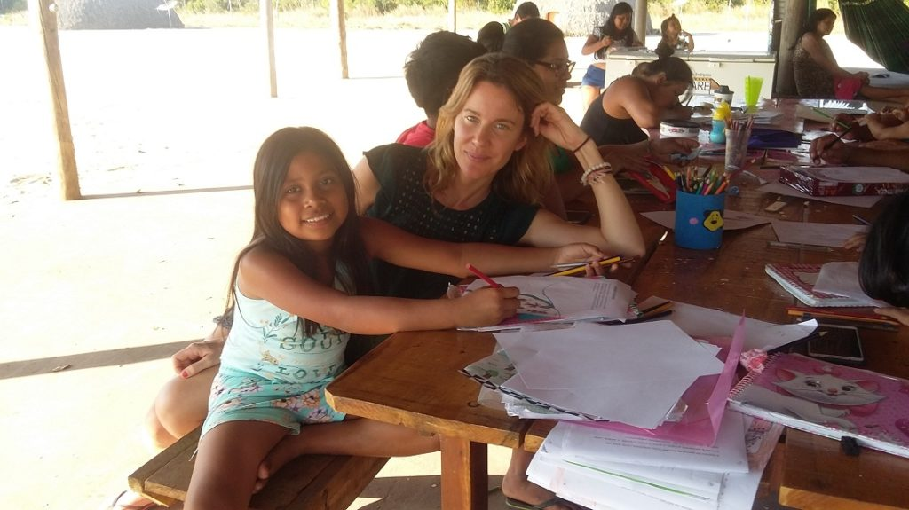 A thin, white woman with long blond hair and light eyes is sat on a wooden bench. Her elbows are resting on a wooden table. In front of her, there is an Indian girl with long, straight, black hair is sitting with a pencil in her hand, she seems to write in a piece of paper. Both are smiling and looking at the camera. We can see other people at the table too. In the background, they're writing and drawing on pieces of papers.