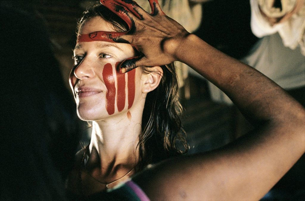 A white woman, with blond and wavy hair and light eyes is looking at the right corner of the image. She has her left cheek painted with three red stripes. In the foreground, in the left corner of the image, an indigenous woman appears on her back. You can only identify part of her hair and left arm with her fingers in red and black paint. She's painting the white woman's face.
