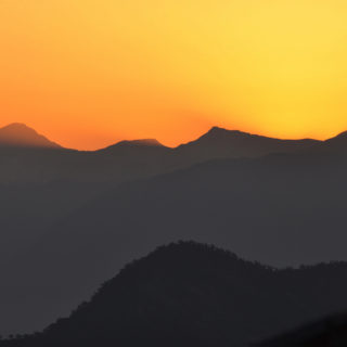 The silhouetted shape of a mountain range occupies the lower half of the photo in dark gray tones. Above the mountains, a dark orange sky at sunset occupies the upper half of the photo.