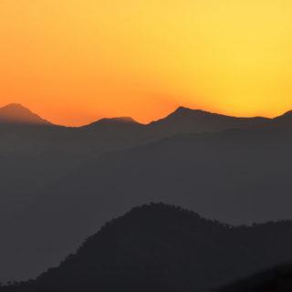 O semblante sombreado de uma paisagem montanhosa ocupa a metade inferior da foto, em tom cinza escuro, quase preto, com o topo das montanhas formando um contorno ondulado na superfície. Sobre essas montanhas, o céu em cor-de-laranja, ao pôr-do-sol, ocupa a metade superior da foto.