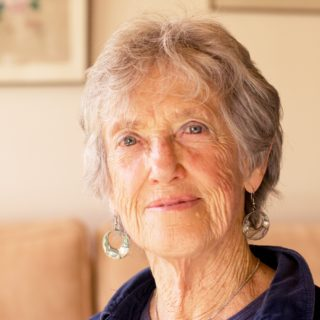 An elderly woman, shown from the shoulders up, with short gray hair and light blue eyes, wearing a blue shirt and earrings with small metal rings. She looks at the camera. In the background is a blurred image of a living room.