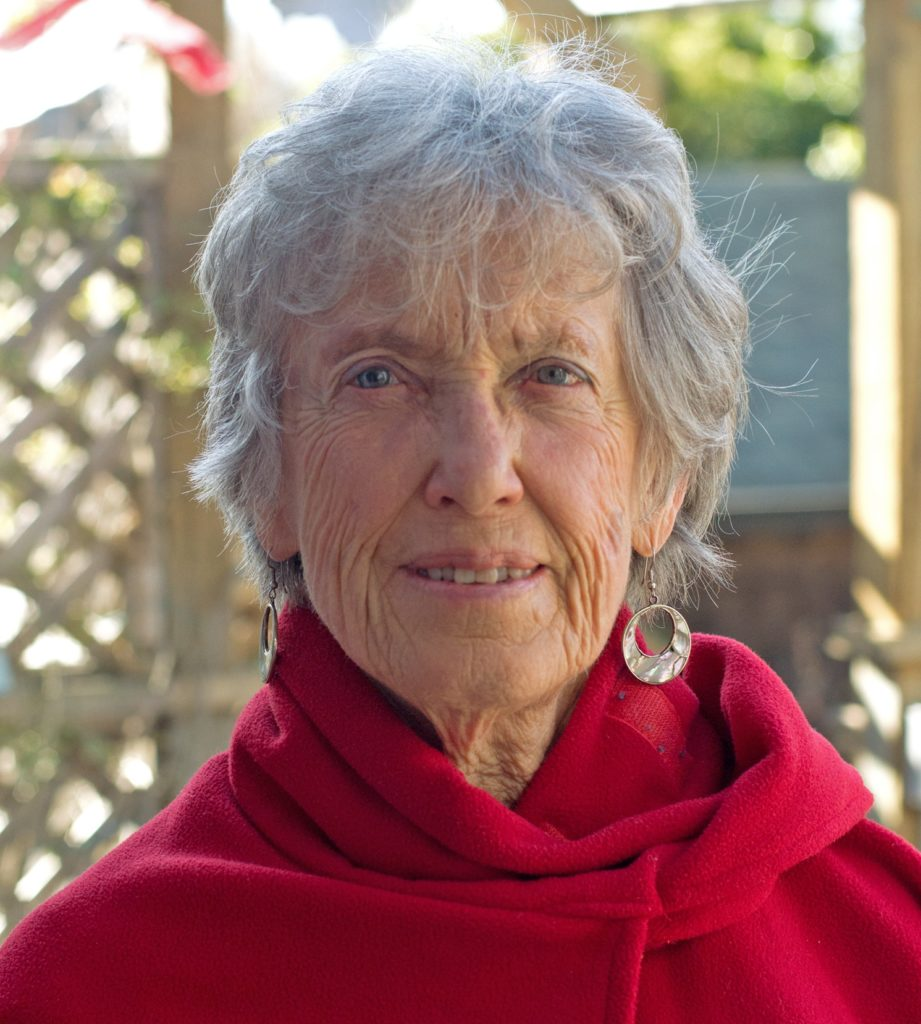 A close-up of an elderly woman's face. She has short gray hair, light blue eyes, and is wearing a red shirt and small metal earrings. She looks at the camera.