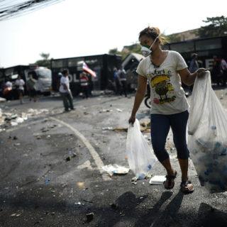 Sobre um chão de asfalto com resíduos diversos espalhados, uma jovem mulher, magra, de cabelos lisos, escuros e longos, presos em um coque, de pele morena e traços orientais, caminha em direção à câmera, carregando dois sacos plásticos grandes, um em cada mão. Os sacos são transparentes e contêm pequenas garrafas PET vazias. A mulher usa sandálias rasteiras pretas, uma calça azul escura, justa, que vai até logo abaixo dos joelhos, e uma camiseta branca com estampas coloridas. Ela usa também uma máscara branca, que cobre sua boca e seu nariz. Ao fundo, aparecem algumas outras pessoas, dispersas, desfocadas.