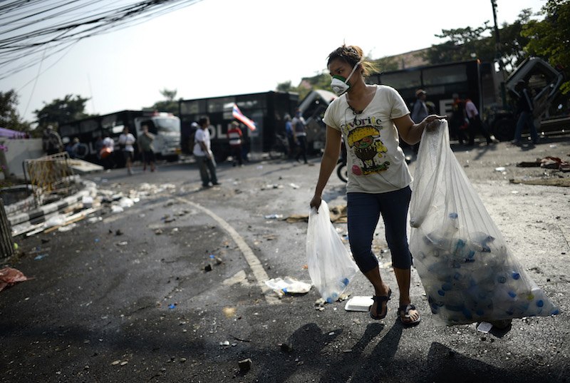 A dark-skinned young woman with straight dark long hair tied in a bun walks towards the camera carrying a large plastic bag in each hand, walking in a street littered with waste. The bags are clear and contain empty plastic bottles. The woman is wearing black sandals, dark blue pants, and a white t-shirt with colorful print. She is also wearing a white mask that covers her nose and mouth. In the background are other people scattered around, out of focus.