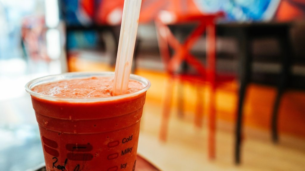 The photo shows a close-up of a clear plastic cup filled with a thick orange drink, with a large clear straw. In the background, out of focus, is the black counter of a café.