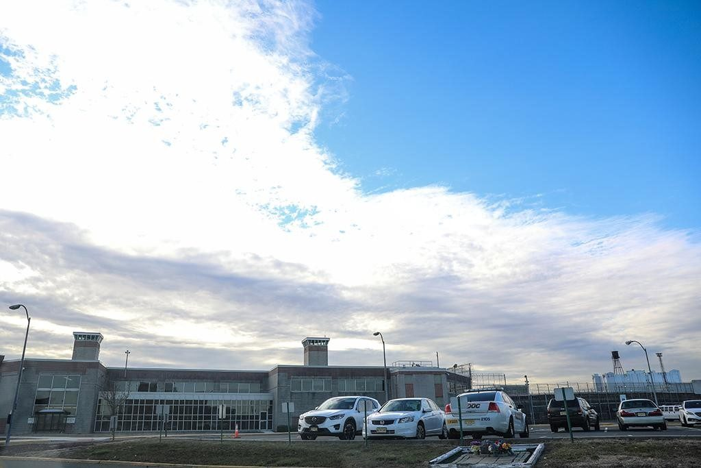 Long shot of a low but wide building, surrounded by walls and fences. Ahead, cars in a parking lot. The sky is blue with white clouds.