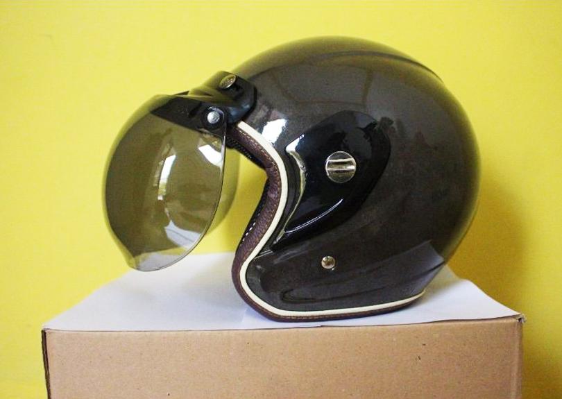 Um capacete de motociclista está virado de frente para a borda esquerda da foto, sobre um suporte cúbico de papelão, de superfície branca e lateral crua, marrom. O capacete é preto reluzente, e tem o vidro frontal escurecido em preto translúcido. O fundo da foto é amarelo liso.