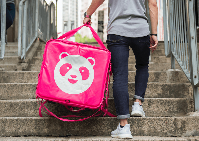 The photo shows the legs and feet of a person wearing white sneakers, dark blue jeans and a light gray t-shirt, walking up a concrete staircase with their back to the camera. They are carrying with their left hand a large bright pink case shaped like a cube, with a white logo shaped like a panda bear's face.
