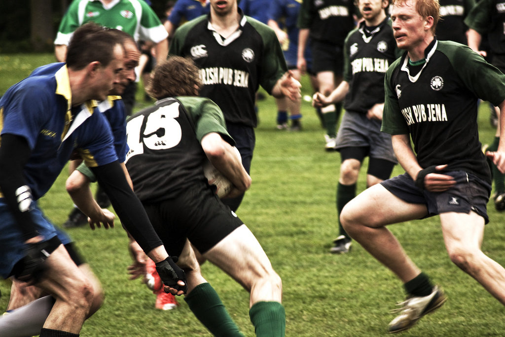 Seven men in uniform are playing rugby on a grass field. Two of them are wearing blue shorts and polo shirts over black long sleeve shirts, as well as black gloves. The rest are wearing black shorts and black shirts with white writing and short green sleeves. All have short straight hair, either blonde or black, and white skin. One of the men is holding a white ball with his back to the camera.