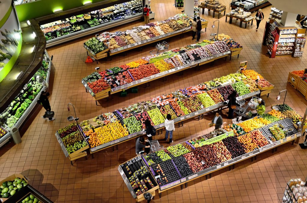 The photo shows fruit and vegetable stands from above, in a variety of colors, inside a supermarket. The floor is brown, made up of square tiles. People are scattered around each stand picking products. In the edges of the photo are other aisles with more products.