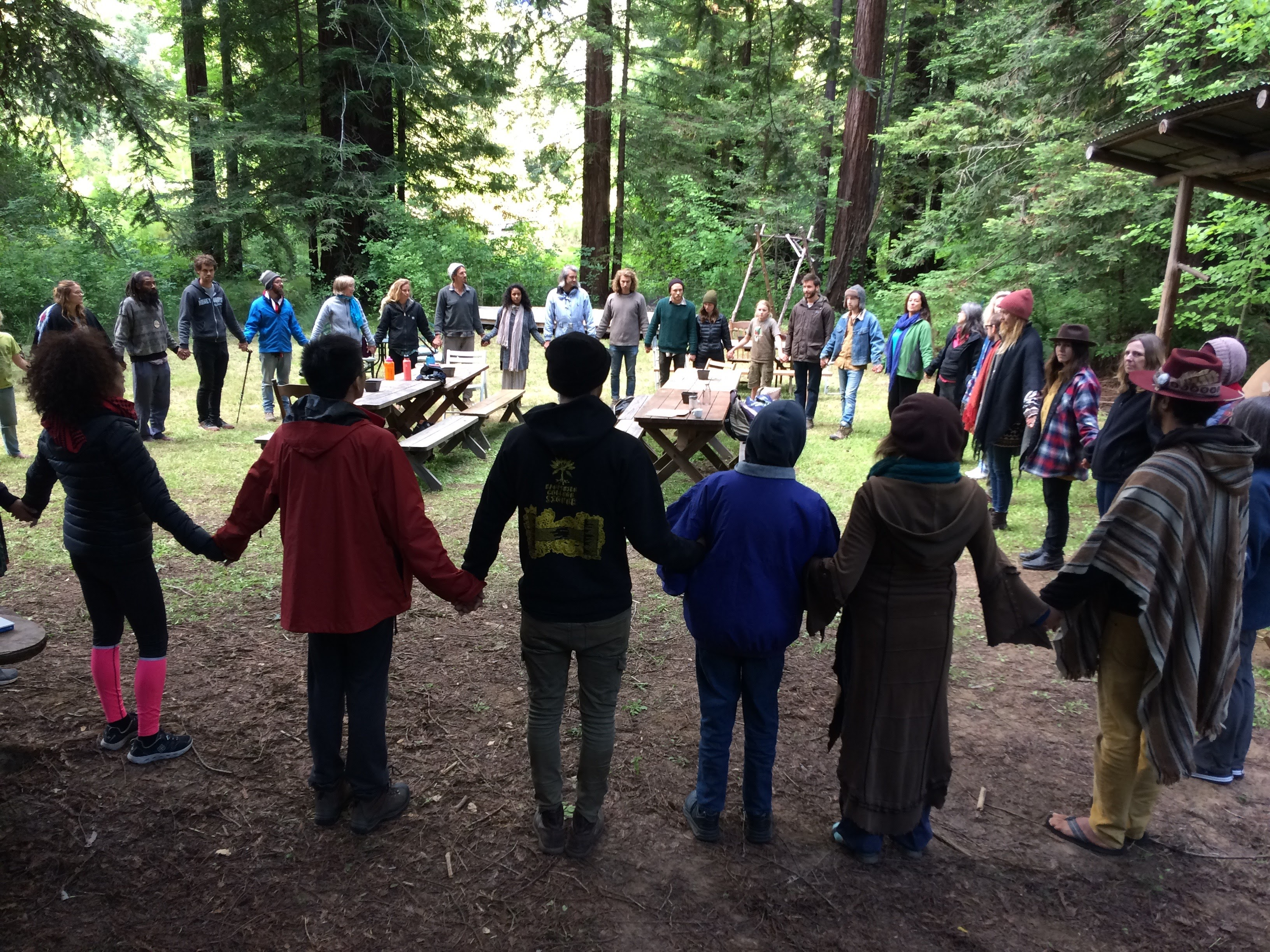 More than 30 people stand in a circle, all holding hands. There are two large wooden tables in the center of their circle. The group is outdoors and in the background there are tall trees.