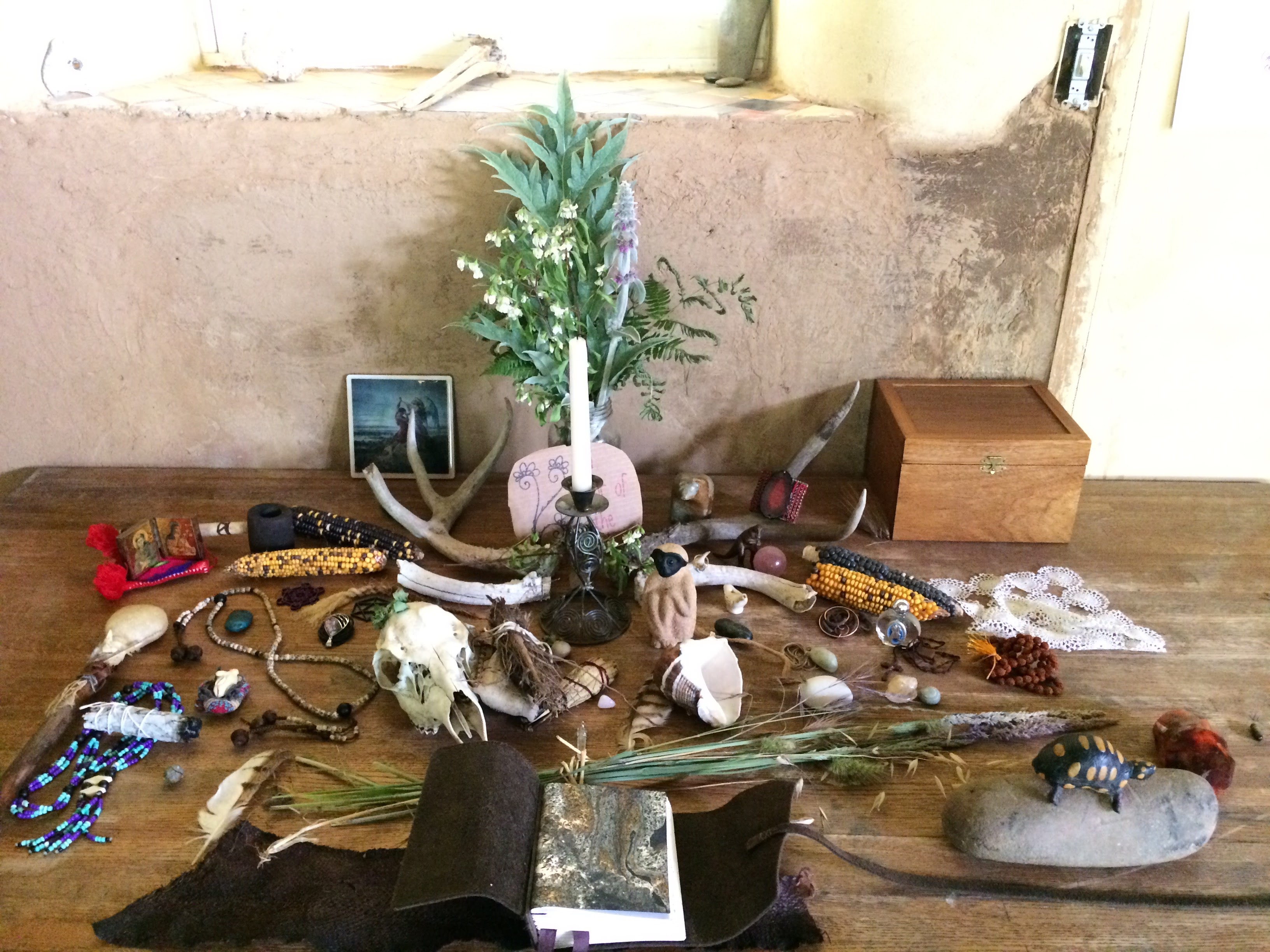 A wooden table holds a collection of objects: A book, some necklaces, stones, a wooden box, a corn husk, some photos and two bunches of leaves.