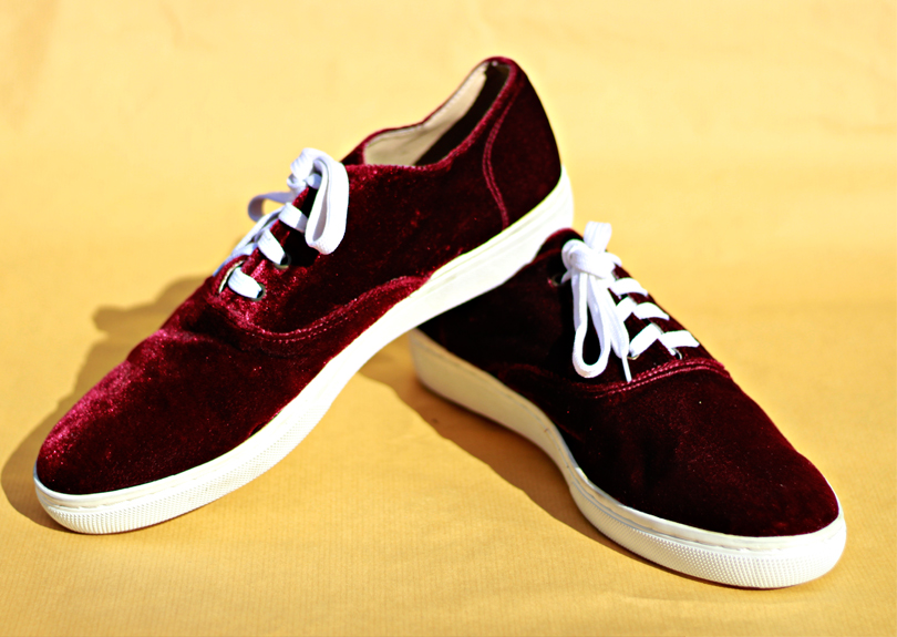 A pair of red suede sneakers with white shoelaces and white sole is arranged in front of the camera on top of a flat yellow background. The right shoe's heel is resting on top of the left shoe's heel.