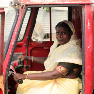 A dark skinned woman with dark eyes and straight black hair is wearing a thin sand colored veil over her head and shoulders and a long skirt made of the same fabric. She is also wearing a dark green shirt with a red and gold stripe at the end of the sleeves and thin golden bracelets. The woman is sitting in the driver's seat of a red truck, holding onto the wheel facing the left of the photo, while looking expressively at the camera. The truck's left door, closest do the camera, is open. In the background is the truck's right door, closed.