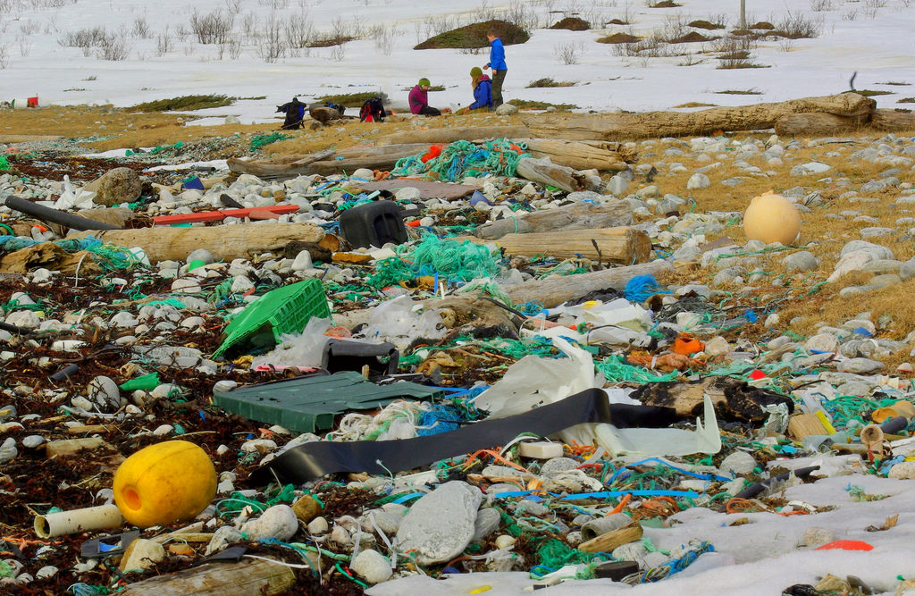 the photo shows a beach covered with a variety of plastic waste. In the back are three people wearing heavy coats with the ground covered with snow.