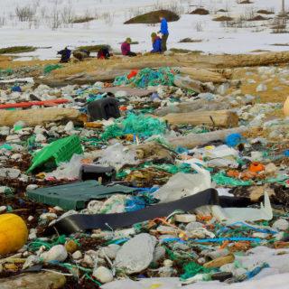 La foto muestra una playa cubierta con una variedad de desechos de plástico. En la parte de atrás hay tres personas que llevan abrigos pesados con el suelo cubierto de nieve.