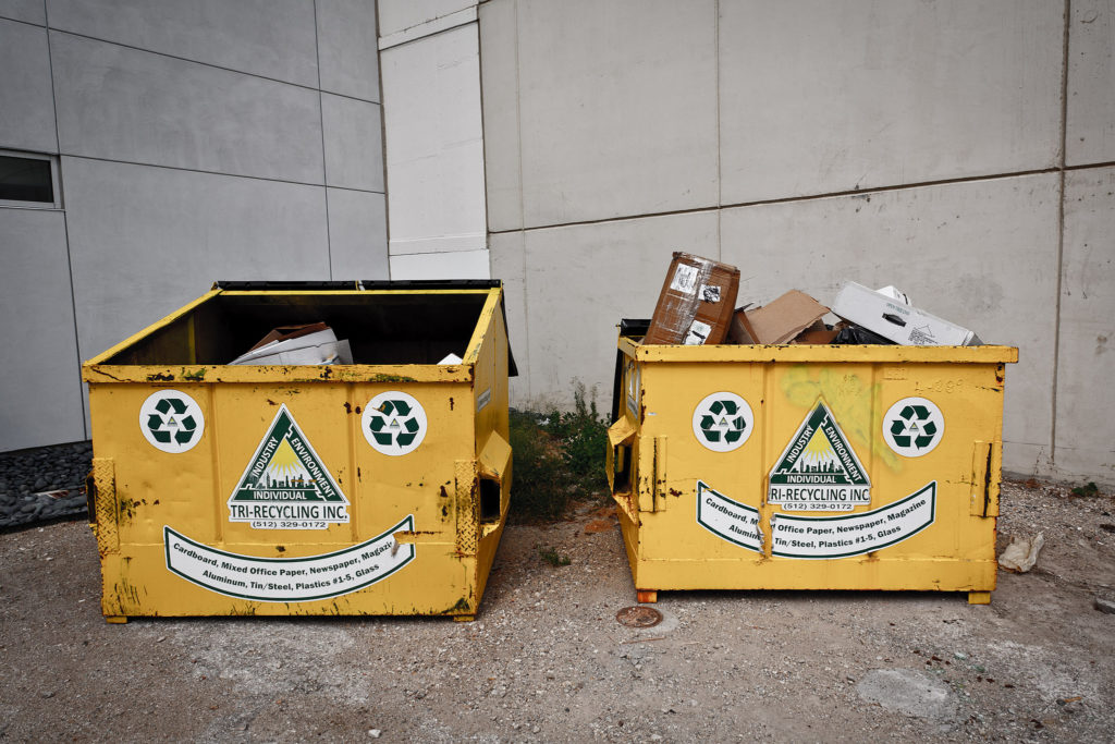 Two large, square metal dumpsters with trash in them. One is full, the other much less so. On the front of each dumpster are stickers arranged in a smiley-face shape.