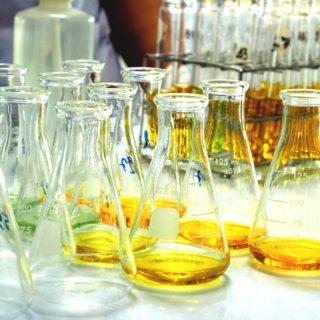 Imagem de um laboratório com diversos frascos transparentes. À esquerda estão vazios, ao meio e à direita estão com uma pequena quantidade de líquido amarelo e verde. Ao fundo e a direita, tubos de ensaio cheios com o mesmo líquido amarelo.