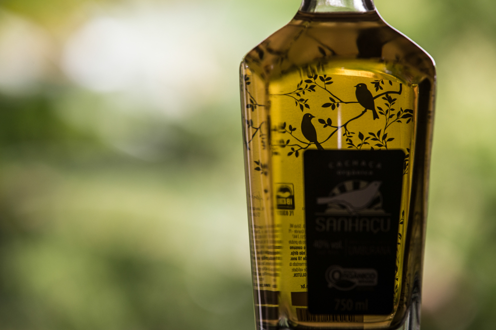 "A glass bottle containing a yellowish, translucent liquid. There's a black seal on the bottle bearing the name ""Sanhaçu."" The company logo shows a white bird in a black and white-striped semicircle. The bottle is also decorated by black, silhouette images of birds perched on leafy tree branches."