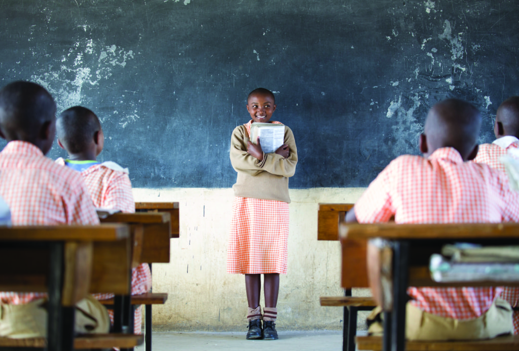 A classroom with a blackboard in the background. In front of the chalkboard stands a black girl with very short hair. She is wearing a beige sweater over a light orange, checkered dress that reaches below her knees. She wears beige socks with two brown stripes, and black sneakers. She holds a book open on her chest. Her face is turned toward the camera, but her gaze is turned to her left. She smiles. There are children sitting on wooden chairs on both sides of the classroom. They are all dark-skinned with very short hair, wearing shirts that match the dress worn by the girl standing in front of the blackboard.