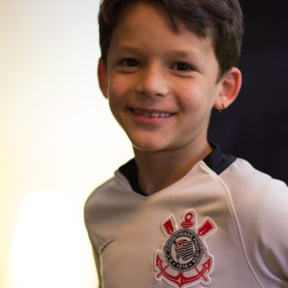 A portrait, from the chest up, of a slender boy with white skin and short brown hair. He is smiling at the camera, and wearing a Corinthians (famous Brazilian soccer club) jersey.