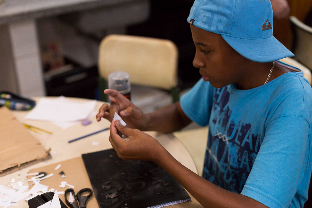 A black boy is wearing a blue T-shirt and a matching cap. He holds a small piece of paper in his hands. He rests his arms on a table. In front of him, on the table, are pieces of paper, scissors and some writing materials (pens and markers).