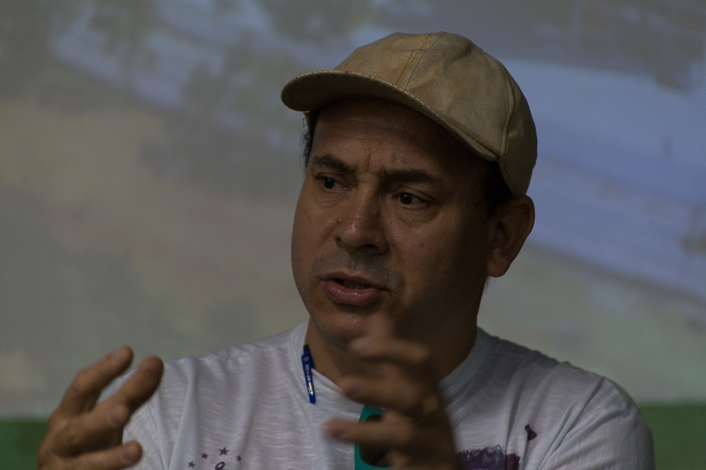 Close-up of a white man wearing a beige cap and a white T-shirt. He looks to his right while gesturing with his hands.
