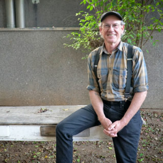 A white man with white hair, wearing a cap and glasses, looks at the camera and smiles. His hands are clasped together. He is standing, but resting his right leg on a wooden bench. He wears a yellow and blue checked shirt with black suspenders and dark blue pants. Behind him is a cluster of small leafy trees with thin trunks, a gray wall and some leaves that have fallen from the tree onto the ground.