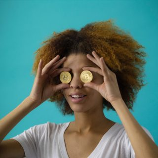 A thin black woman wearing a white t-shirt is holding up two coins with a B (the symbol for Bitcoin) over her eyes. Her hair is curly and blonde. The background is blue.