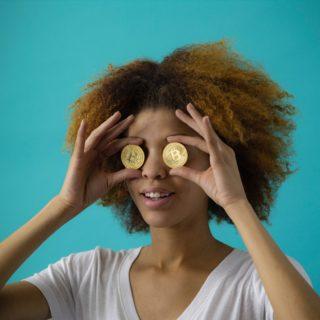 Una mujer negra, delgada, con una camiseta blanca, sujeta dos monedas con una B (símbolo de la moneda virtual bitcoin) sobre sus ojos. Su pelo es rizado y rubio, en una melena corta. El fondo de la imagen es azul.