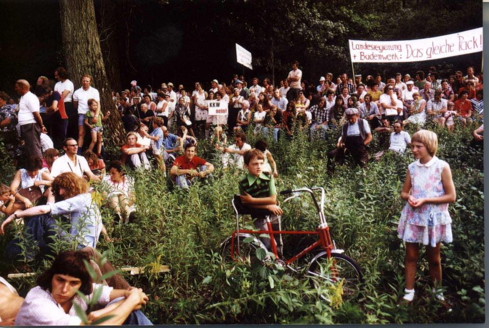A group of people, children and adults, sitting in a green field wearing summer clothes, holding up protest signs.