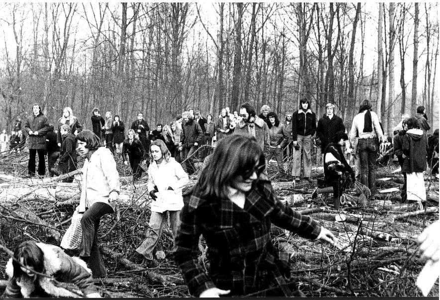 In black and white, a large group of people, dressed in winter clothes, walking into a forest. The ground is covered with naked branches. In the background are tall trees without leaves.