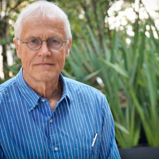 A white-haired, white-skinned man is wearing round, metal-framed glasses and a light blue shirt with white stripes. He is shown from the chest up. He looks at the camera with a serious expression. In the background, slightly blurred, are some plants.