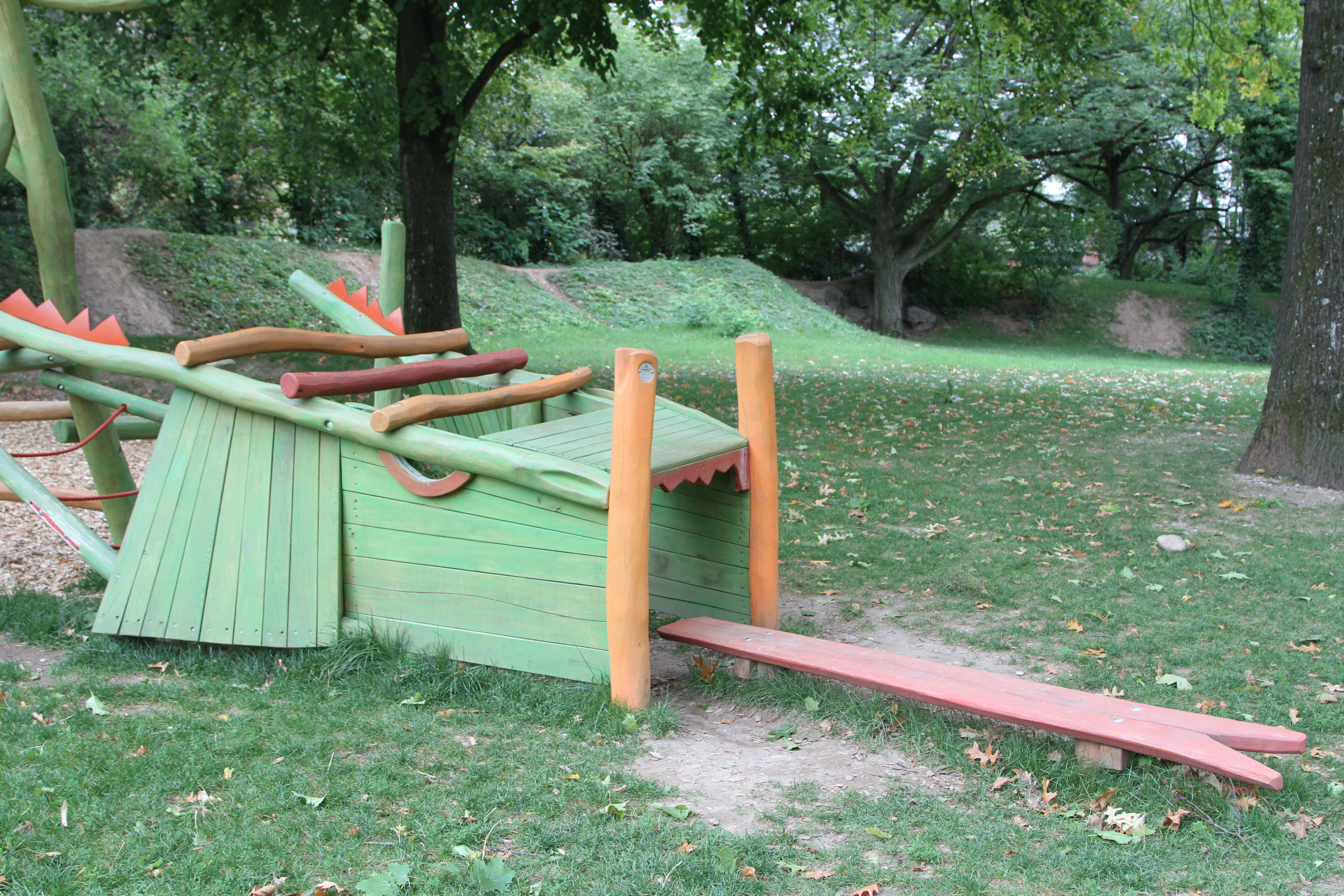 A wooden play structure, painted green, yellow and brown. In the background, grass and trees.