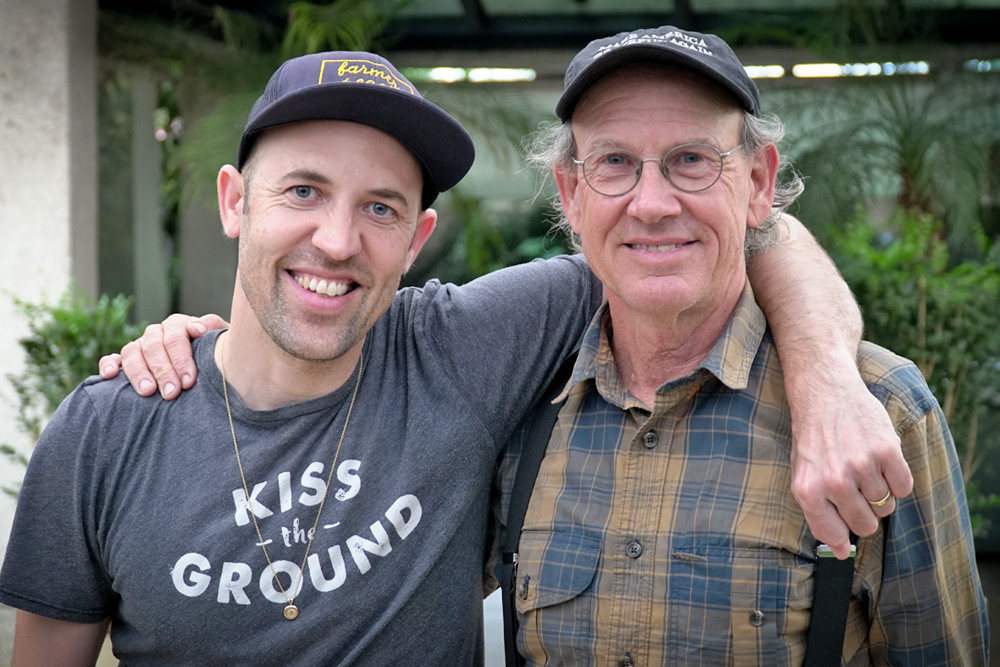"On the left, a bald, white man in a purple cap and a gray T-shirt bearing the slogan ""Kiss the Ground."" With his left arm, he embraces the man from the previous photo, who is older than he is. The older man is wearing a cap and a yellow and blue checked shirt with black suspenders. His right hand rests on the younger man's left shoulder. Both look at the camera and smile."