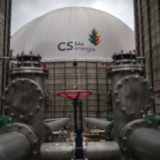 "At the center of the photo, towards the back and in focus, is the white dome of a chemical plant. Written in black is the name ""CS bioenergia,"" along with the company's logo - a blue droplet below a pine tree that is half green, half orange. There are two tall gray walls flanking the dome on each side, and metal piping in the foreground."