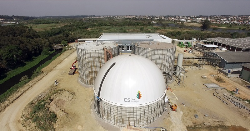 In the center is a gray and white chemical plant. The same white dome from the cover photo, with CS Bioenergia's name and logo on it. Behind the dome are two equally large round structures. Further back is a white, rectangular structure. The plant is built on dirt ground, surrounded by trees. Further in the background is a body of water and, further back, the outskirts of a city.