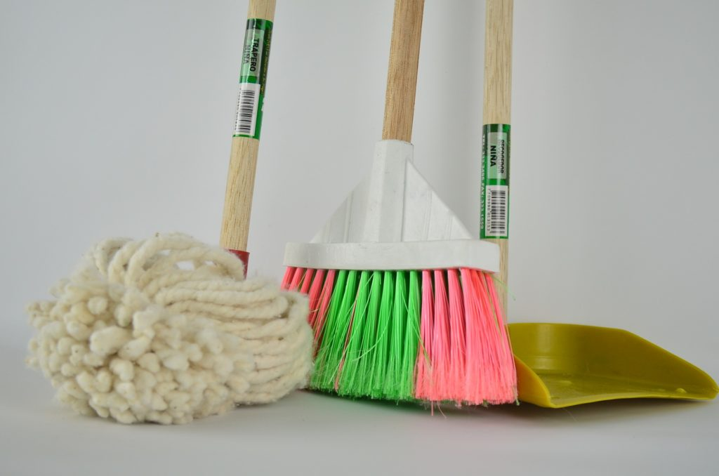 Against a white background, a mop, a broom and a dustpan, all with wooden handles. The mop is on the left, a pink and green bristle broom in the middle, and on the right, a yellow plastic dustpan.