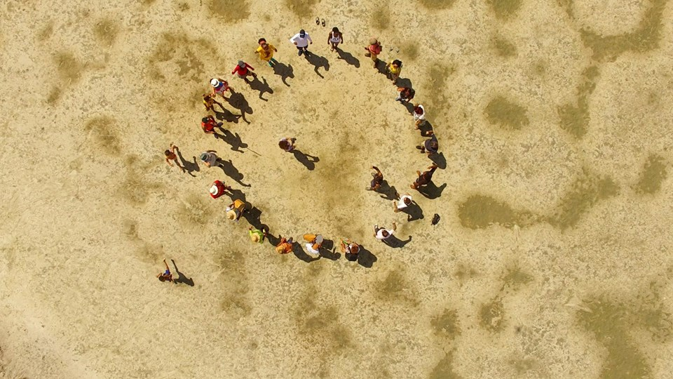 - An aerial photo of approximately 25 people standing in a circle on the ground. Two people are inside the circle and two others are outside. The ground is sand-colored with some darker patches.